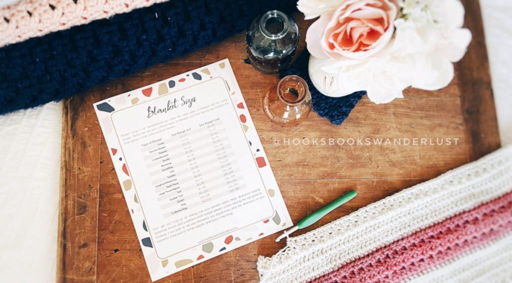 A printed copy of HB&W's Blanket Sizes Cheat Sheet lays on a wooden drafting board next to a blue glass vase, an amber glass vase, and a bouquet of cream and peachy pink flowers, a stack of finished blankets to the top of the photo and a blanket in progress with a green crochet hook below it.